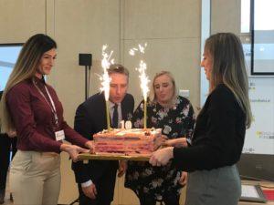 Dwie kobiety trzymają tort urodzinowy z racami. zdmuchnięcie świeczek na urodzinowym torcie przez i Dyrektorkę Oddziału Magdalenę Bobrowską oraz Prezesa Zarządu Przemysława Żydoka